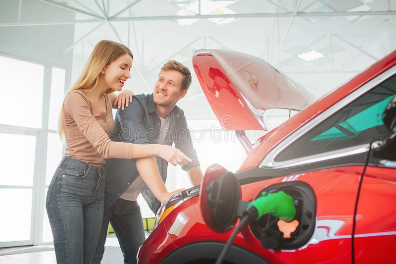 Young smiling family buying first electric car in the showroom. Attractive pleasantly surprised woman point at eco stock photography