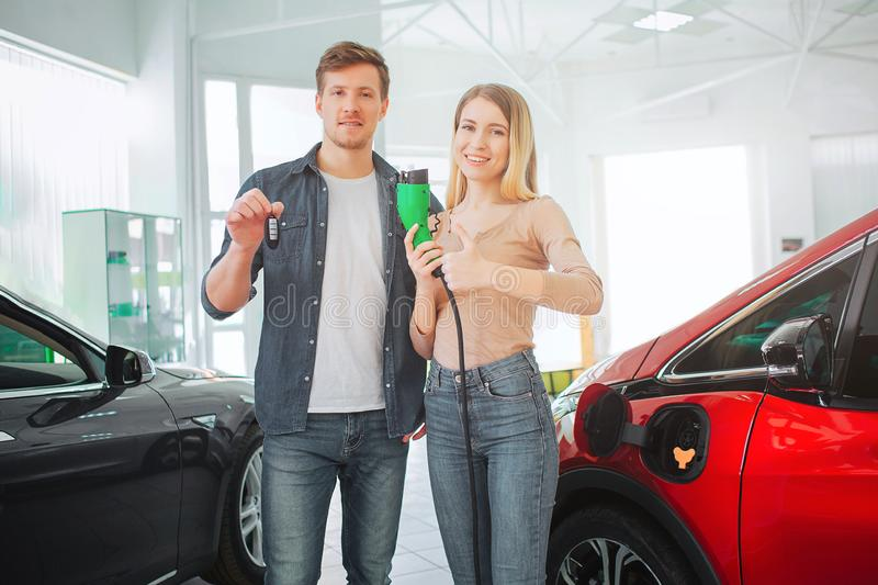 Young smiling family buying first electric car in the showroom. Environmental protection. Attractive man and woman royalty free stock photography