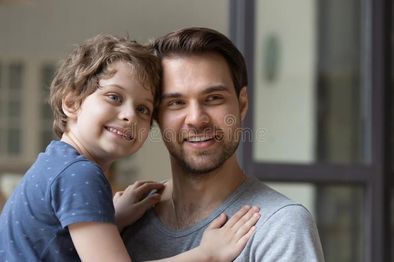 Young smiling father holding little preschool son on hands. Head shot portrait young smiling father holding little preschool son on hands, looking aside. Happy royalty free stock photo