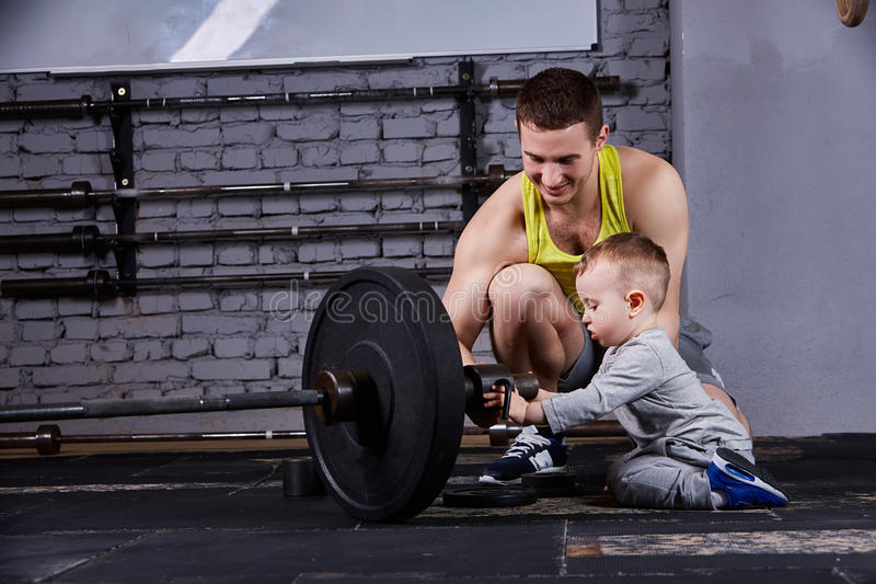 Young smiling father and little cute son with dumbbells against brick wall at the cross fit gym. Sportsman and little boy in the sportwear and sportive shoes stock photos