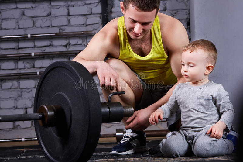 Young smiling father shows little son the dumbbell against brick wall at the cross fit gym. Sportsman and little boy in the sportwear and sportive shoes. Happy royalty free stock images
