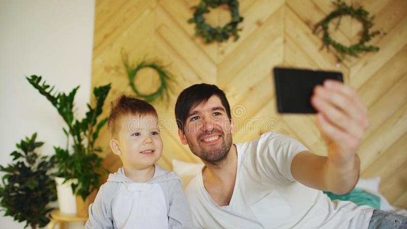 Young smiling father with son on bed taking selfie photo with smartphone camera. At home royalty free stock photography