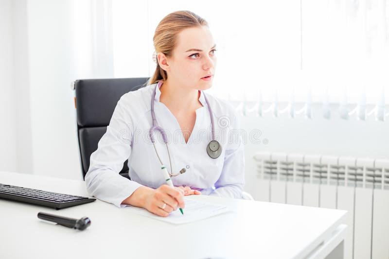 Young smiling female blonde doctor sitting at the desk with a pen and stethoscope royalty free stock photos