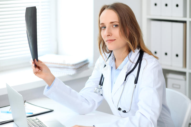 Young smiling female doctor looking at x-ray while sitting at the table near window stock photography
