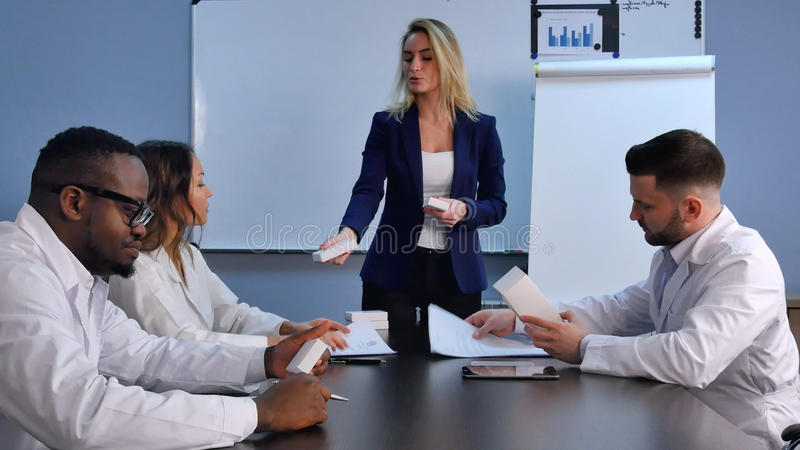 Young smiling female doctor presenting a white unlabeled box of pills stock photos