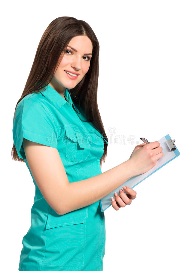 Young smiling female doctor in uniform with clipboard writting stock image