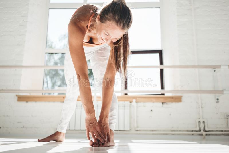 Young smiling female doing stretching exercises leg indoor white gym royalty free stock images