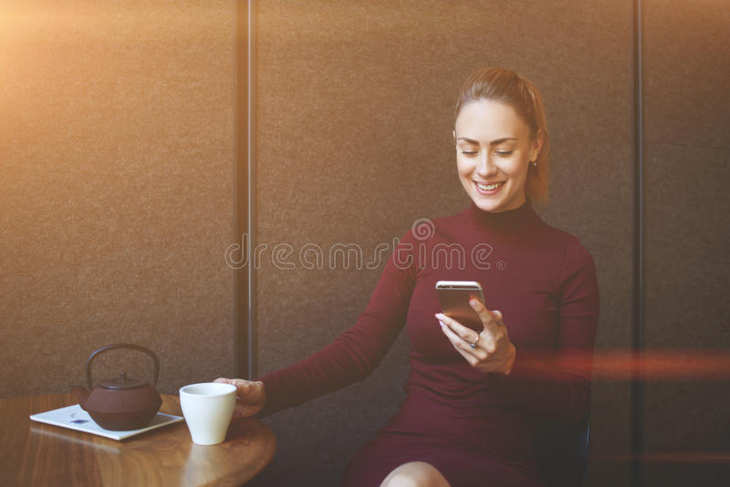 Young smiling female reading text message on mobile phone while resting in coffee shop interior stock photos