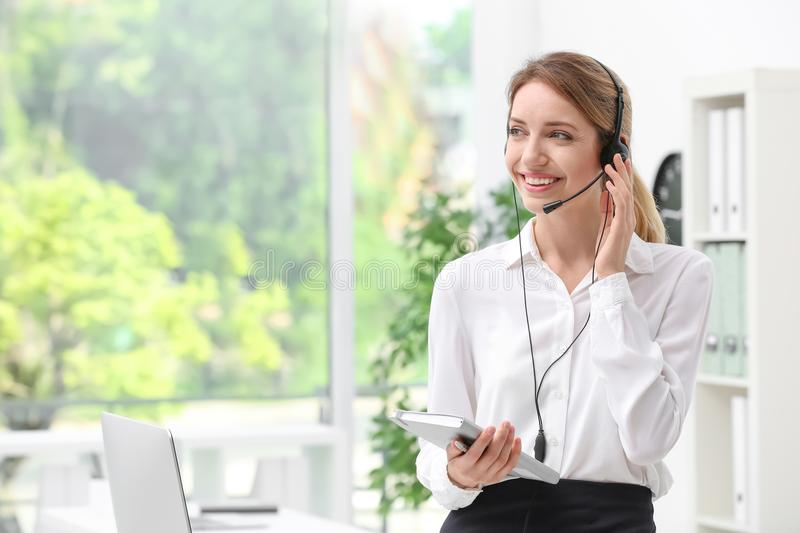 Young female receptionist with headset in office. Young smiling female receptionist with headset in office stock photo