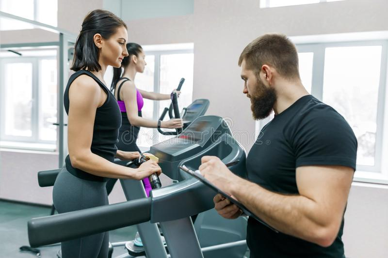Young smiling fitness women with personal trainer an adult athletic man on treadmill in the gym. Sport, teamwork, training, stock images