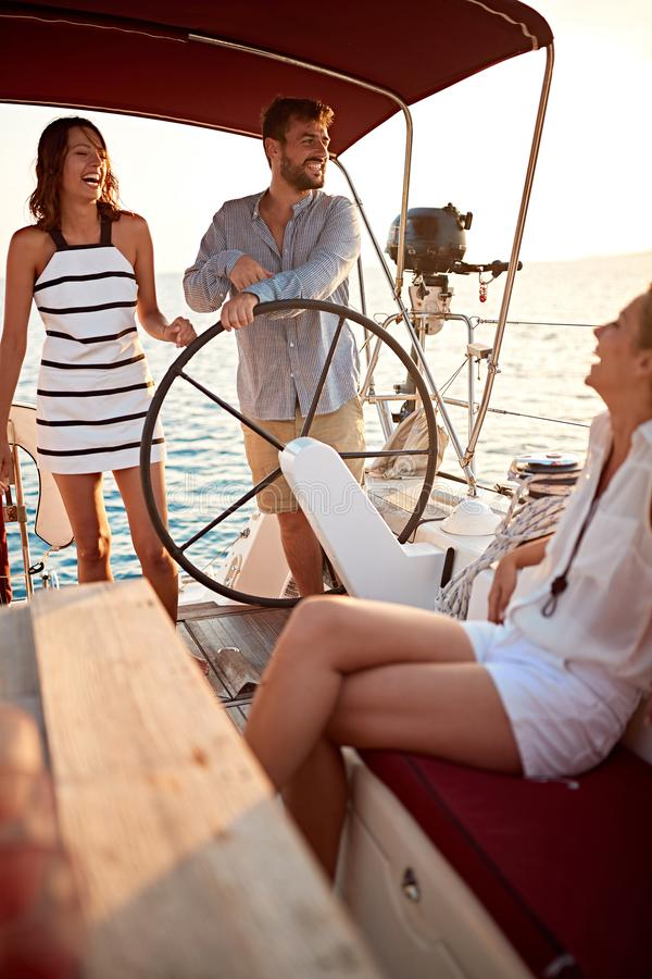 Young friends sailing on boat together and enjoy at sunset on vacation royalty free stock photos
