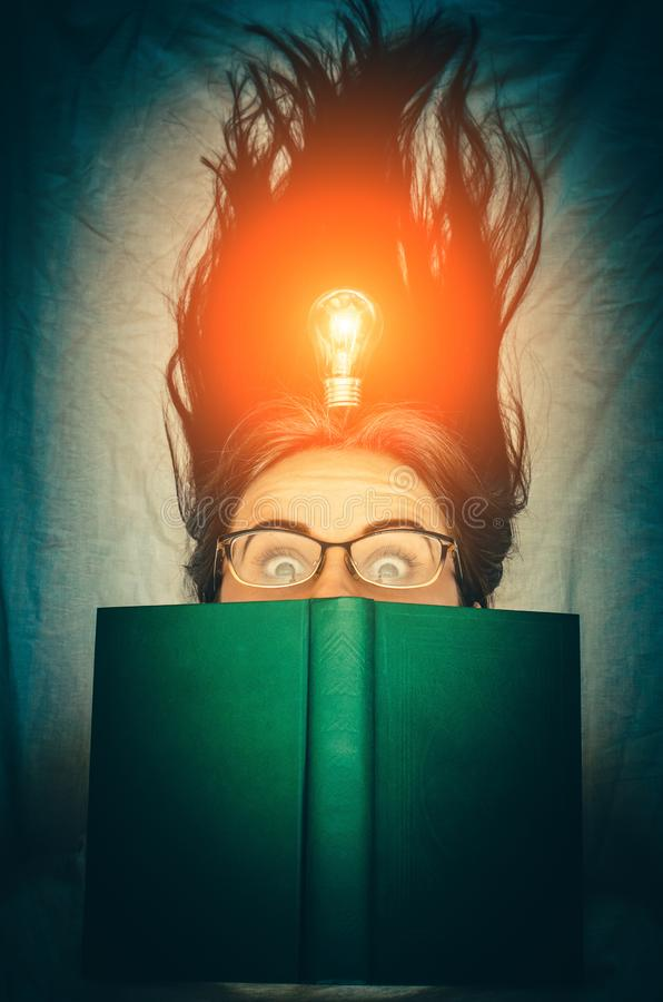 Young smiling girl with a book and a glowing bulb as a concept of fresh idea and inspiration. Young smiling brunette girl with a book and a glowing bulb as a stock image
