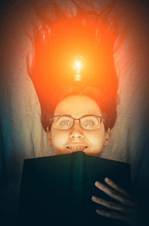 Young smiling girl with a book and a glowing bulb as a concept of fresh idea and inspiration. Young smiling brunette girl with a book and a glowing bulb as a stock photography