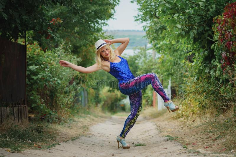 Young smiling girl in colored leggings, blue top, white hat and on high heels dancing. On the dirt road stock images