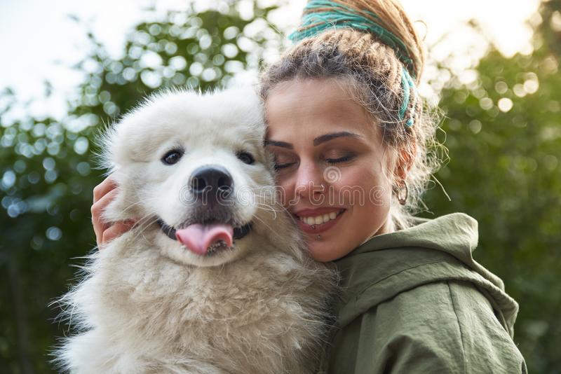 Young smiling girl with colorful dreads with a satisfied happy expression he closed his eyes and hugs his beloved dog royalty free stock images