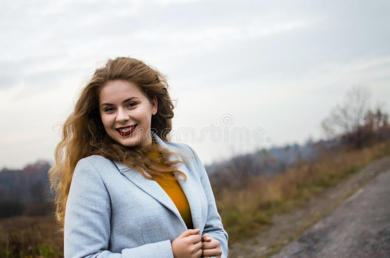 Young smiling girl with curly hair. On the background stock photos