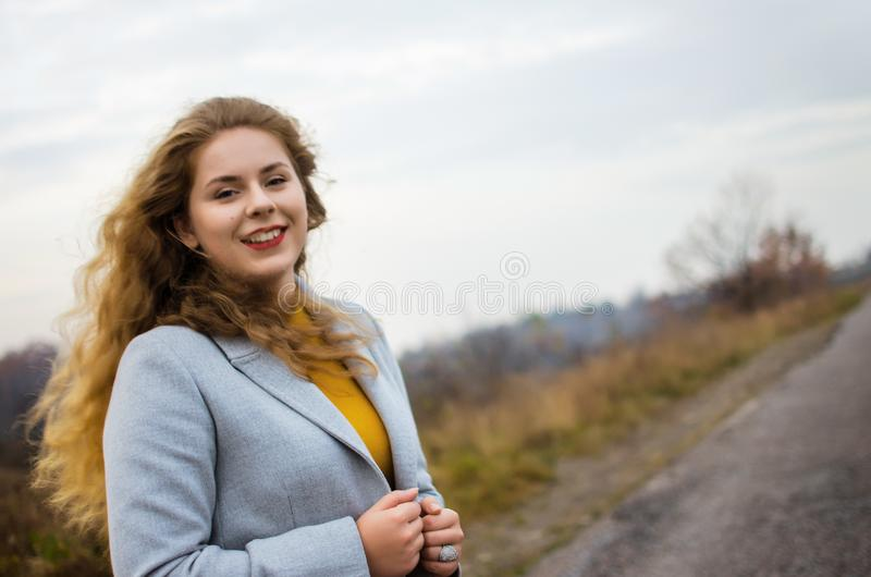 Young smiling girl with curly hair. On the background royalty free stock photography