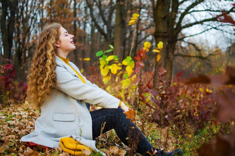 Young smiling girl with curly hair. On the background stock images