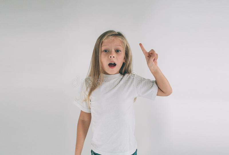Young smiling girl having a good idea. Portrait of an excited child in white T-shirt pointing finger up at copyspace stock image