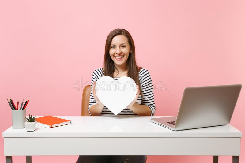 Young smiling girl holding white heart with copy space working on project while sitting at office with laptop isolated royalty free stock photo