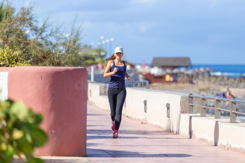 Young smiling girl jogging on the embankment in the morning royalty free stock photography
