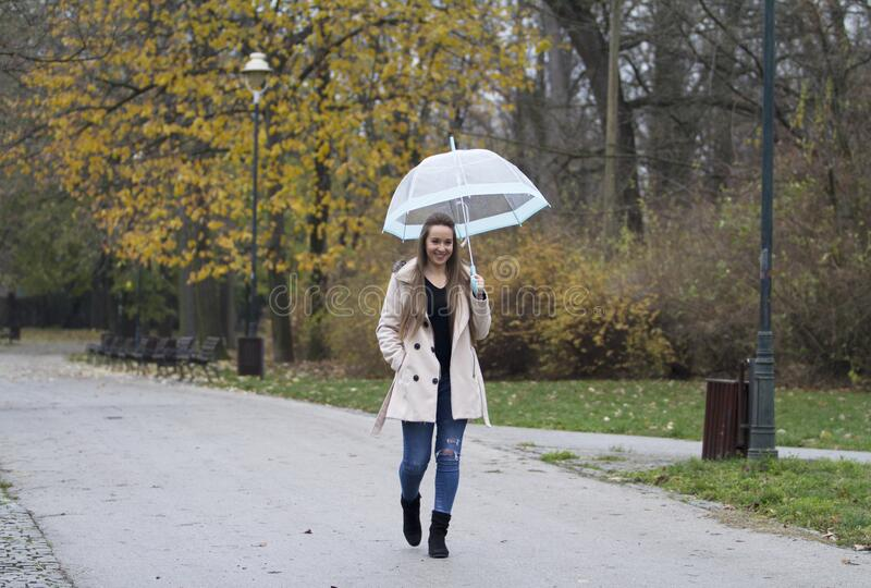 A young smiling girl with long hair. Holds an umbrella in her hand and walks in the park. Young smiling girl with long hair. Holds an umbrella in her hand and royalty free stock image