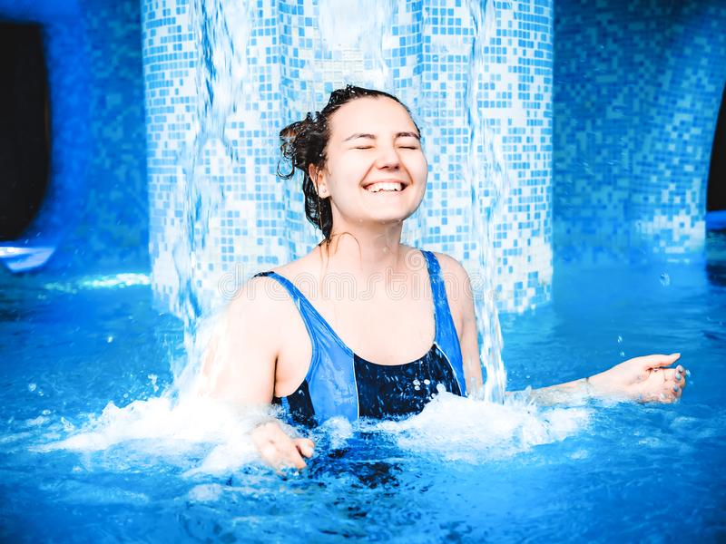A young smiling girl swimming in the pool with blue clear water. A girl is standing under a stream of water. Pure stream stock image