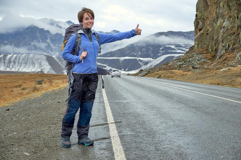 A young smiling girl is traveling in the mountains. stops the car on the road, hitchhiking, raises his hand. A young smiling girl is traveling in the mountains royalty free stock photo