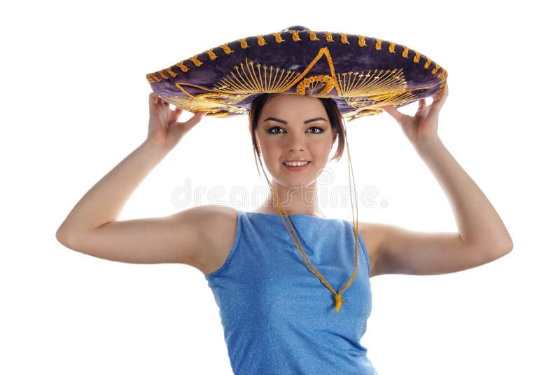 Young smiling girl trying on Mexican sombrero. Portrait on white background stock image