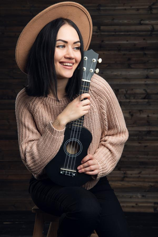 Young smiling girl with a ukulele sit in studio on a wooden background. stock photography