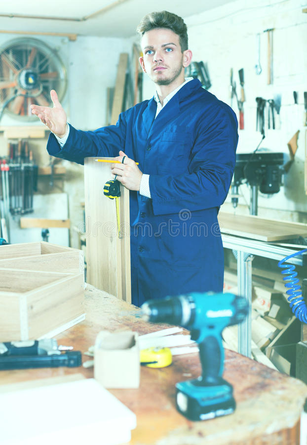 Young smiling guy taking measurements for furniture stock photo