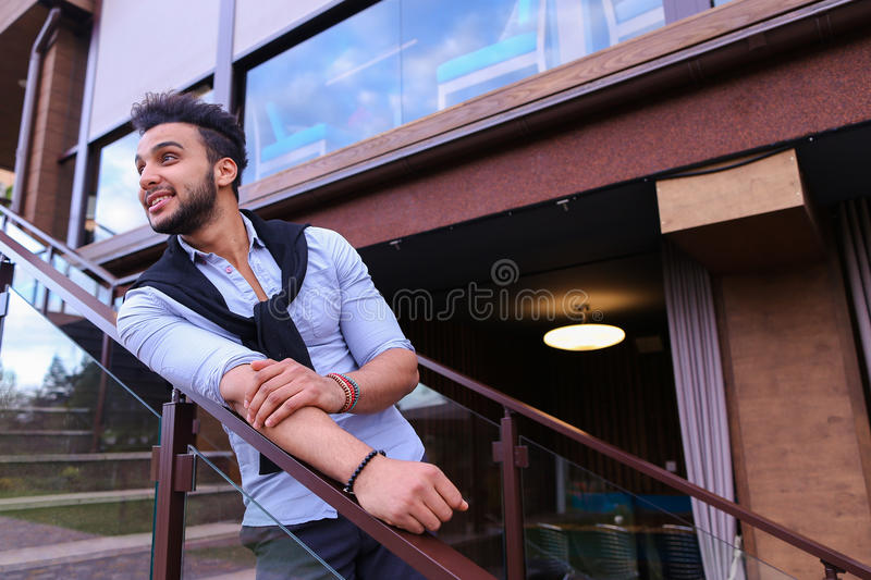 Young smiling handsome male Arab appearance leaning on breast ha. Cute Arabian businessman student posing for catalog of brand of men`s clothing, went to stock photos