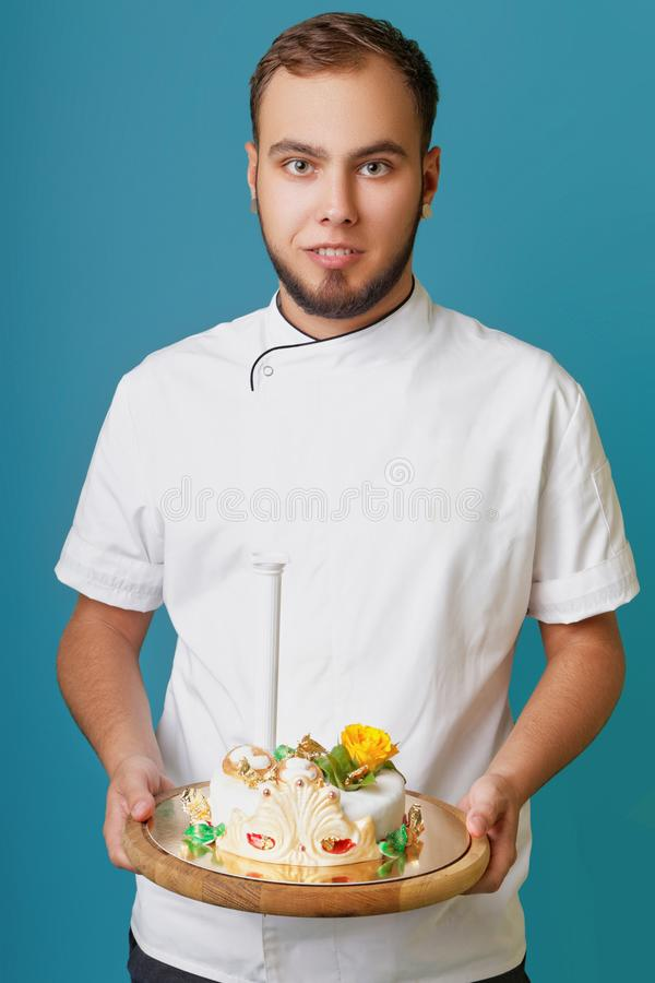 Young male confectioner in a tunic with cake in the studio stock photo
