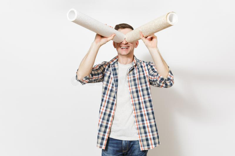 Young smiling handsome man in casual clothes looks through wallpaper roll as with binoculars or spyglass isolated on. White background. Instruments for royalty free stock photo