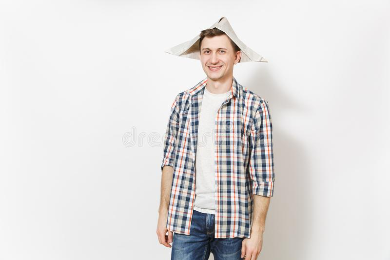 Young smiling handsome man in casual clothes and newspaper hat isolated on white background. Accessories for renovation royalty free stock photos