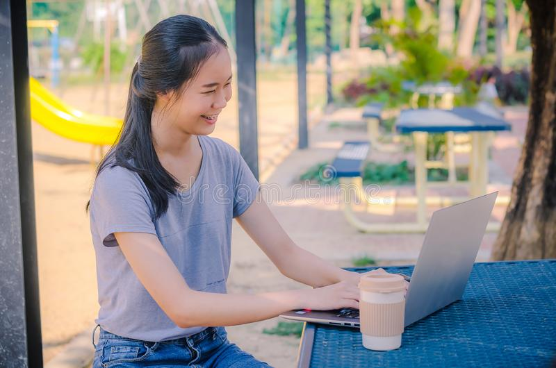 Young smiling hipster girl using laptop for work while sitting on a table in the park royalty free stock images