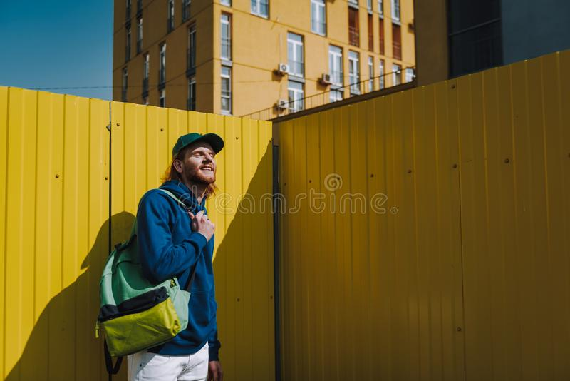Young smiling hipster man enjoying sun shine. Urban lifestyle and activity. Waist up portrait of young smiling hipster guy closing eyes on sun shine while stock photography