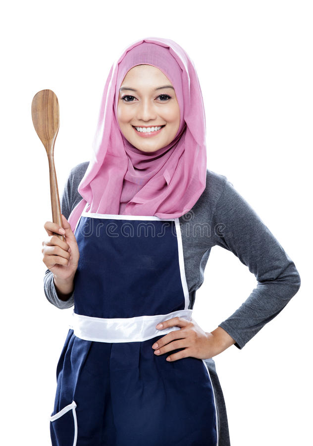 Young smiling housewife holding a wooden spatula royalty free stock photography