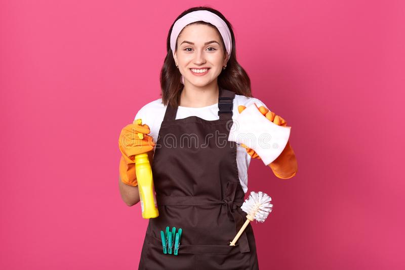 Young smiling housewife wearing hair band, brown apron and white casual t shiert, posing isolated over pink background. Mad woman royalty free stock images