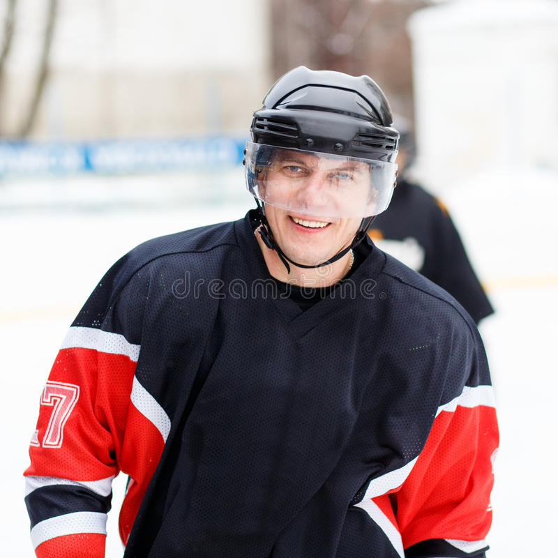 Young smiling ice hockey player in helmet and gear. Young smiling ice hockey player in helmet and protective gear on ice hockey competition stock photography