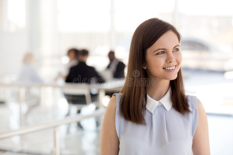 Young smiling intern looking away dreaming of success, future vi. Young smiling intern looking away dreaming of success, ambitious millennial female employee royalty free stock image