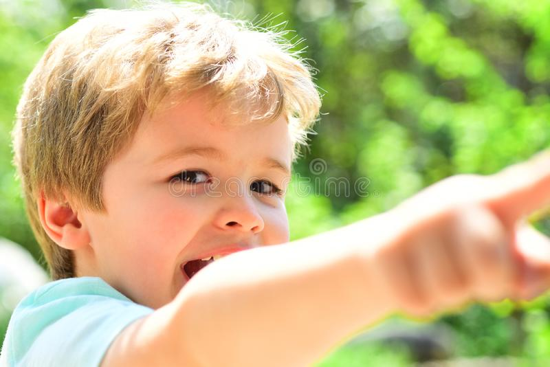 Young smiling kid point at something happily. Cheerful child has found sometinhg. Scincere happy emotions from young royalty free stock photography