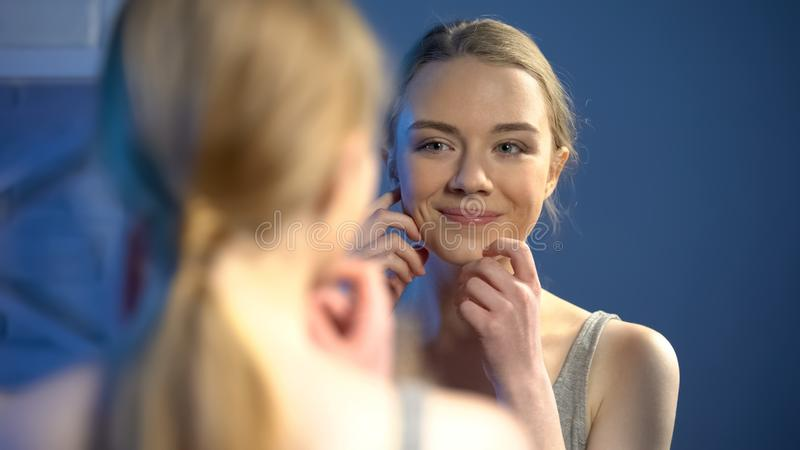 Young smiling lady looking at mirror reflection, happy with skin treatment stock photos