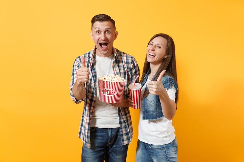 Young smiling laughing couple woman man watching movie film on date holding bucket of popcorn plastic cup of soda or stock image