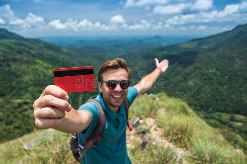 Young smiling male showing empty credit card. He is standing on top of mountain and showing the outdoor beauty. stock photo