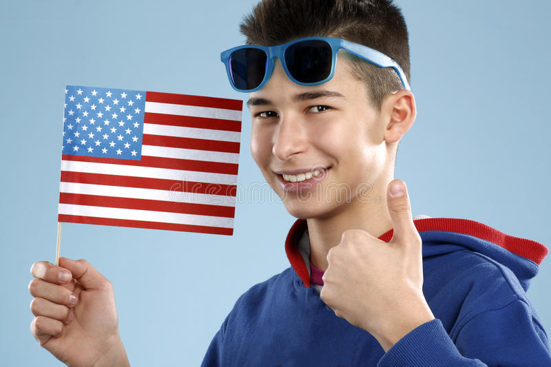 Young smiling male student teenager holding a flag. On blue royalty free stock photo