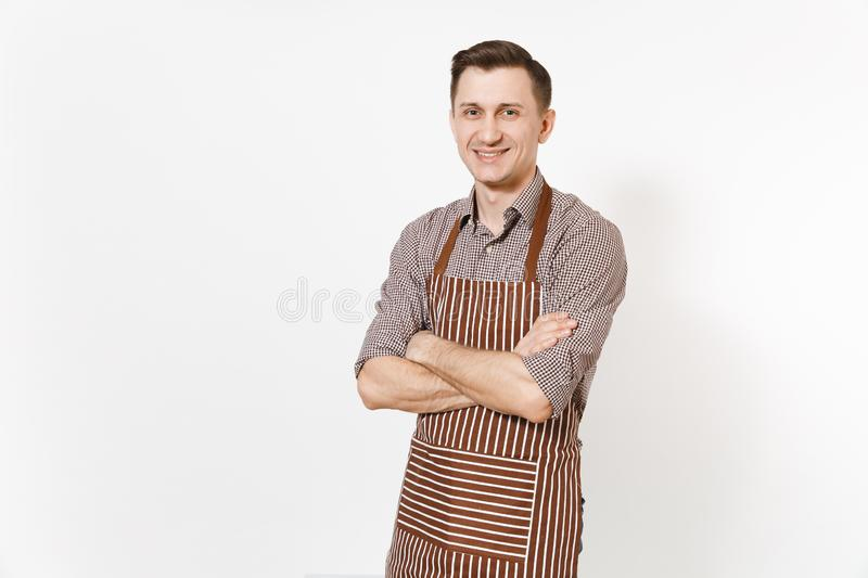 Young smiling man chef or waiter holding hands folded in striped brown apron, shirt isolated on white background. Male royalty free stock images