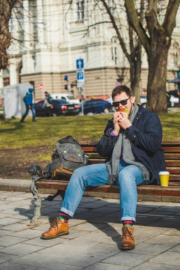 young smiling man eating burger and drink coffee sitting on city bench stock photos