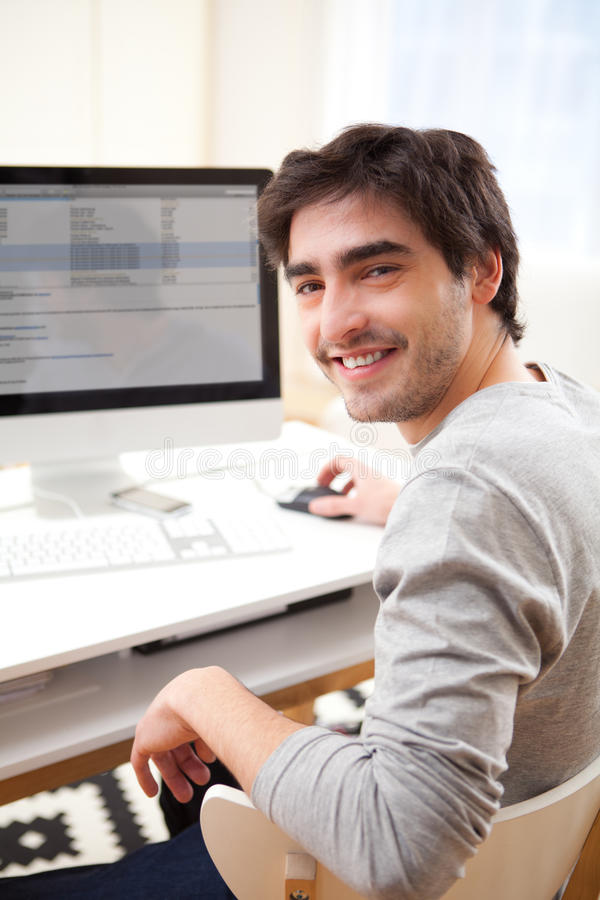 Young smiling man in front of computer royalty free stock image