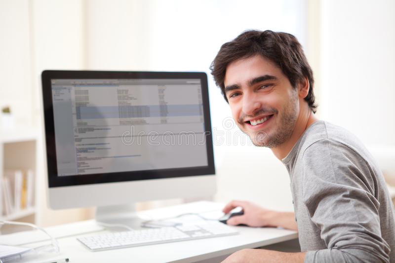 Young smiling man in front of computer stock image
